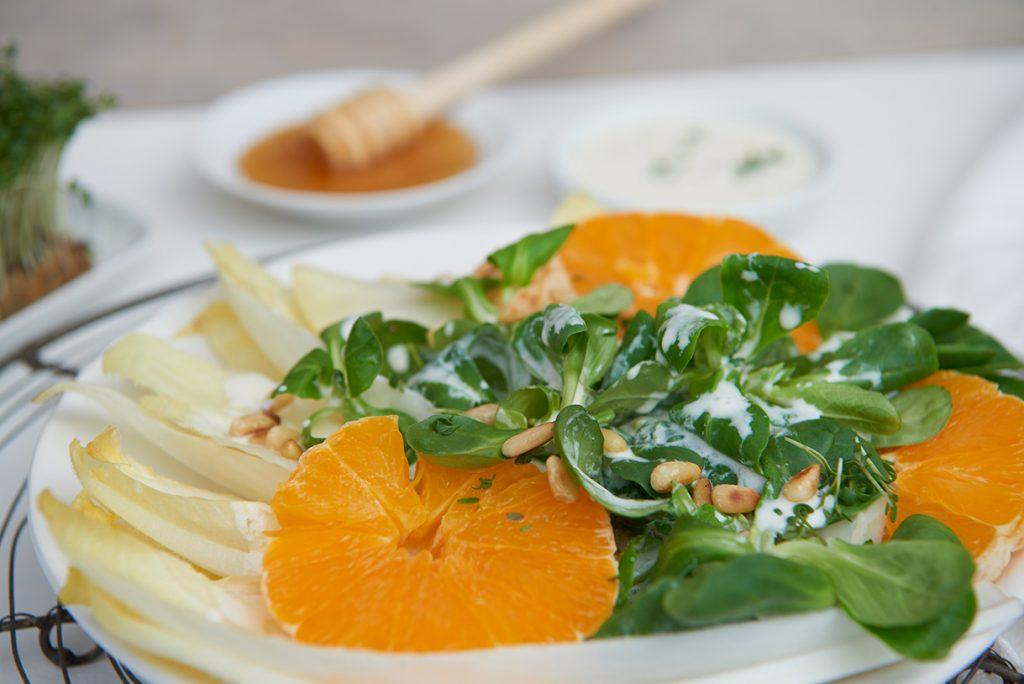 chicoree-orangen-salat-mit-fruchtdressing-und-pinienkernen-auf-teller-foto-maike-helbig-fuer-www.myotherstories.de